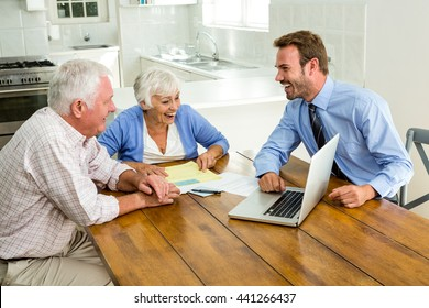 Couple laughing with agent sitting at table in home