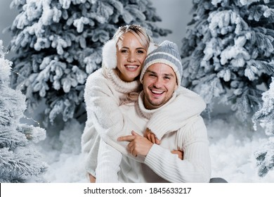 Couple couple laughing and having fun while snow falls near christmass trees. Winter holidays. Love story of young couple weared white pullovers. Happy man and young woman hug each other.