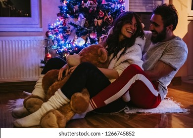 Couple laughing and hugging in front of the Christmas tree. Girl is holding Teddy bear