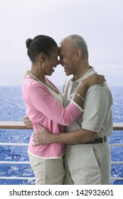 Couple laughing and hugging on cruise ship