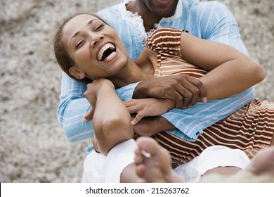 Couple laughing, man embracing woman, close-up