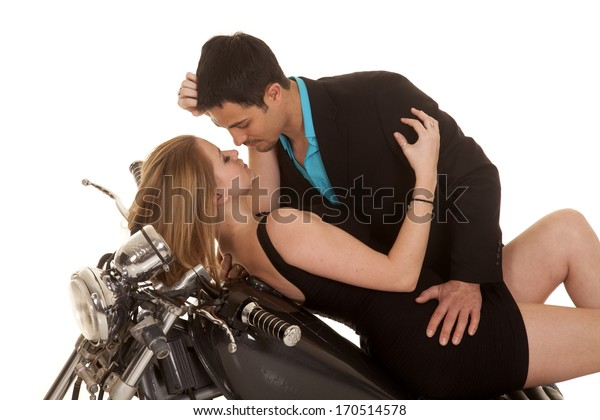 A couple laying back on her motorcycle getting ready to kiss.