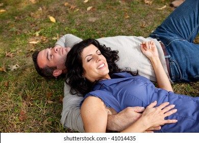 A couple laying on grass in a park