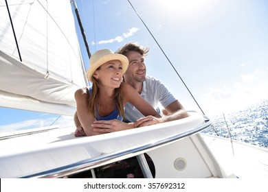 Couple laying on a sailboat deck during cruise