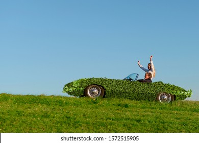Couple in leaf covered sports car