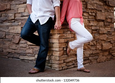 Couple Leaning Against Wall Holding Hands