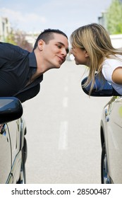 couple leaning out of car windows and kissing. Copy space