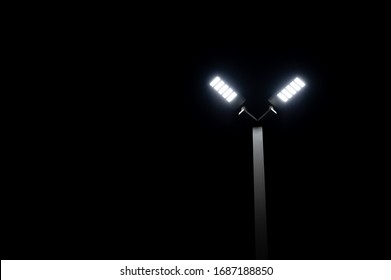 A couple of LED street light glows under the night time dark sky