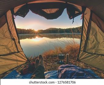 Im Zelt am See ruhen die Couponbeine. Wanderer genießen Ausblick nach draußen und Wanderurlaub gratis