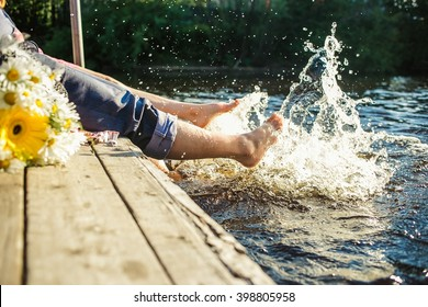 Couple legs in the water splashing with bouquet of  flowers. Summer joy