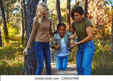 A couple of lesbian ladies having fun in the autumn park with their teenage daughter. The young women entertaining the kid. The girl has the help of her female parents as she attempts to jump high.