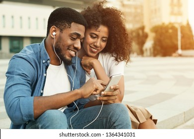 Couple listening to music with earbuds from smartphone, walking in city