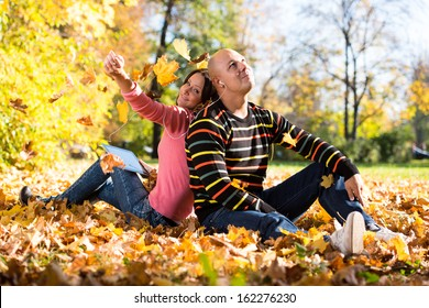 Couple Listening To Music On Autumn Leaves