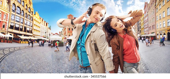 Couple listening to the music, over urban background