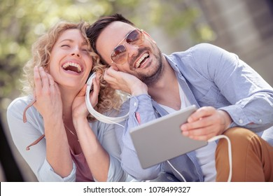 Couple listening to music together while sitting in a city park.People,love,music and happiness concept.