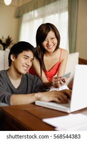 Couple in living room, with laptop and calculator