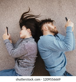 Couple in living room using smart phones. Lack of communication, technology overuse.