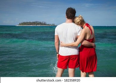 Couple Loking at The Sean with Desert Island in Background