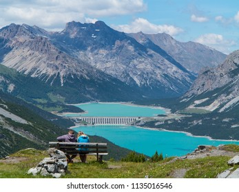 Couple look a panorama sit on a bench, lake of Cancano in Valtellina