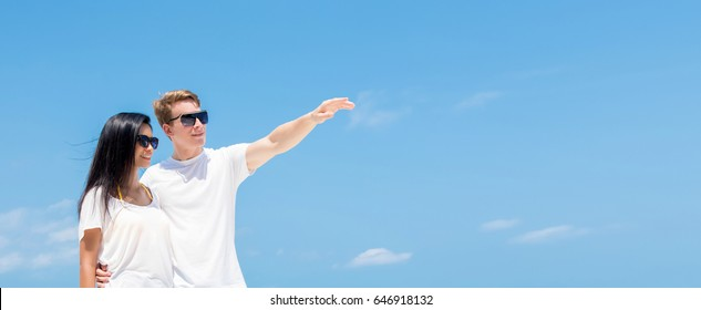 Couple looking away in fresh summer sky background - panoramic banner with copy space