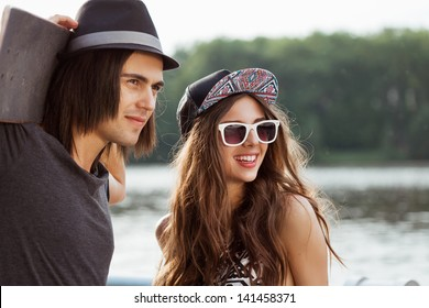 Couple looking away on the bank of a river. Young active people. Outdoors, lifestyle