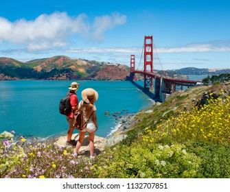 Couple looking at beautiful summer coastal landscape, on hiking trip. Friends  relaxing on mountain. Golden Gate Bridge, over Pacific Ocean and San Francisco Bay, San Francisco, California, USA.
