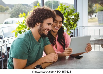 Couple looking at digital tablet in cafeteria