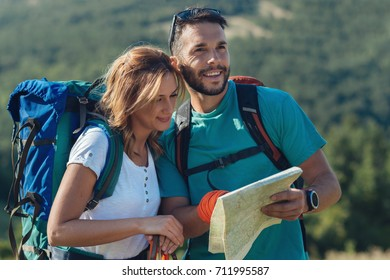 Couple looking for directions on a map.Hikers.