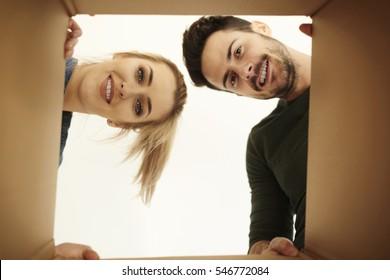 Couple looking down at camera through cardboard box