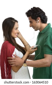 Couple looking at each other while listening to music on a mobile phone