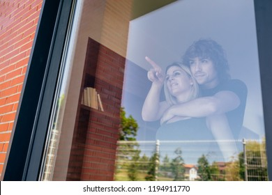 Couple looking at the garden of their new house through the window