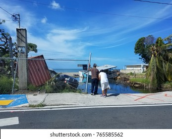 couple looking at house and lot badly damaged by hurricanes in Puerto Rico