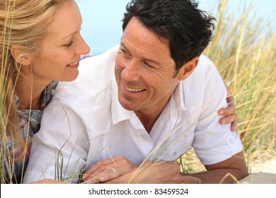 Couple looking into each others eyes on the sand.
