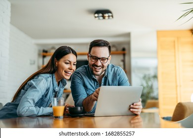 Couple looking at laptop computer together, at home, front view, portrait.
