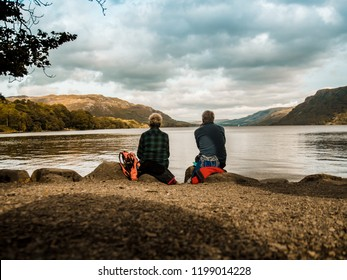 Couple looking at the magnificent view of a lake between mountains