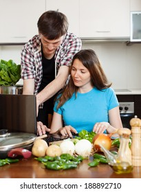 couple looking notebook during cooking vegetables at  kitchen