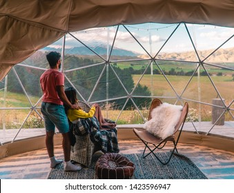 Couple looking out at nature from geo dome tents. Green, blue, orange background. Cozy, camping, glamping, holiday, vacation, romantic lifestyle concept. Outdoors cabin, scenic background. New Zealand
