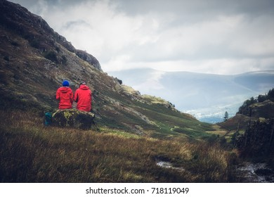 couple looking over the fells in the lake district wearing red cumbria england UK. Man and woman. Male Female.