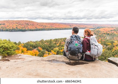 Couple looking at panorama from the top of the rocks. Two young hikers staring at the beautiful view below them with colourful trees all around. Wanderlust feeling, hiking and nature concepts.