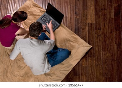Couple looking at a screen together. He is pointing at the screen. Horizontally framed shot.