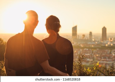 A couple looking at the skyline of the French city of Lyon during a summer sunrise.