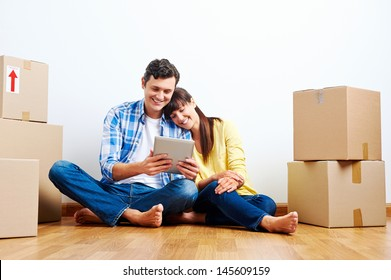 couple looking at tablet while moving into new home with boxes