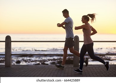 Couple looking at their fitness tracking app while running along the ocean at sunset, fit active lifestyle