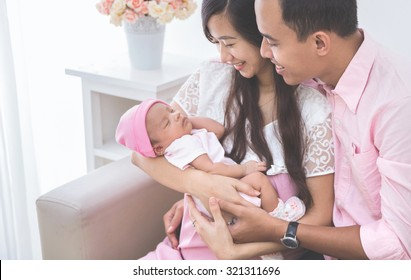 Couple looking at their sleeping baby girl, close up