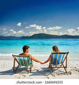 Couple in loungers on a tropical beach at Thailand