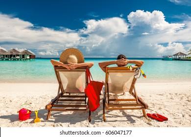 Pareja en tumbonas en una playa tropical de Maldivas