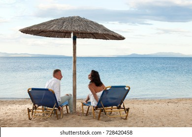 Couple in loungers on a tropical beach at Maldives. Back view of a couple on a tropical beach. Funny photo. Honeymoon. Love story. Freedom concept. Romantic lovers. Romance. Love you. Life. Dream.