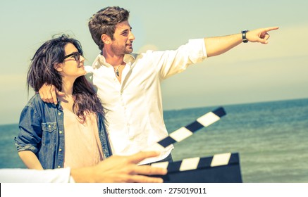 Couple in love acting for romantic movie at beach - Cinema industry concept with ciak slate - Confident guy and happy girlfriend modern lifestyle - Focus on male face and soft vintage filtered look