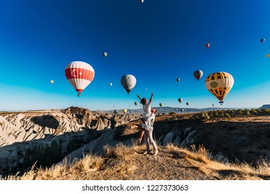 Couple in love among balloons. A guy proposes to a girl. Couple in love in Cappadocia. Couple in Turkey. Honeymoon in the mountains. Man and woman traveling. Flying on balloons. Wedding. Journey. Love