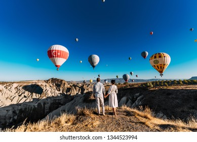 Couple in love among balloons. Loving couple rear view. Couple in love in Cappadocia. Couple in Turkey. Honeymoon in the mountains. Man and woman traveling. Flying on balloons. Wedding. Journey. Love